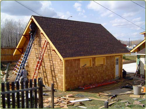image of a carpenter installing western red cedar shingles as siding for a garage
